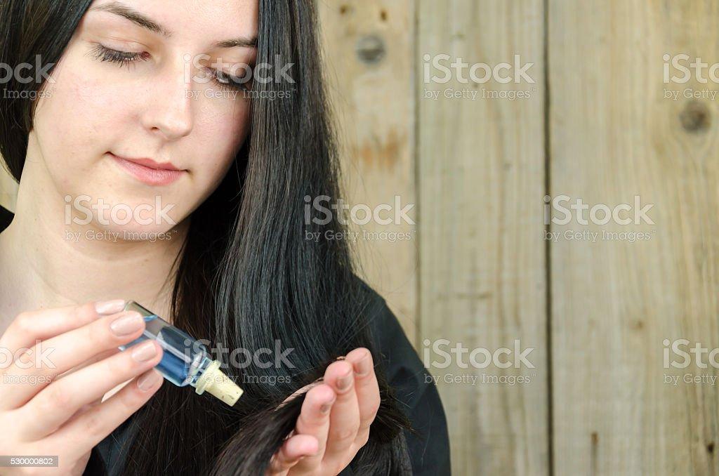 Bela adolescente lubrifica e nutre os cabelos - foto de acervo