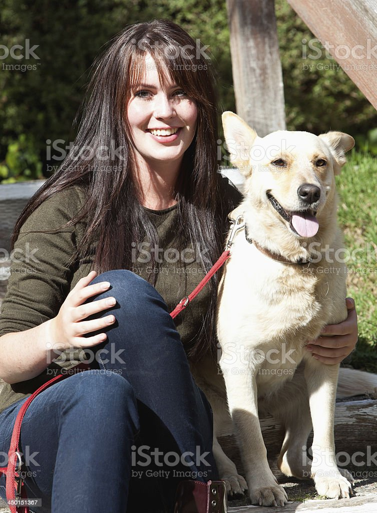 beautiful teenager sitting with her dog royalty-free stock photo