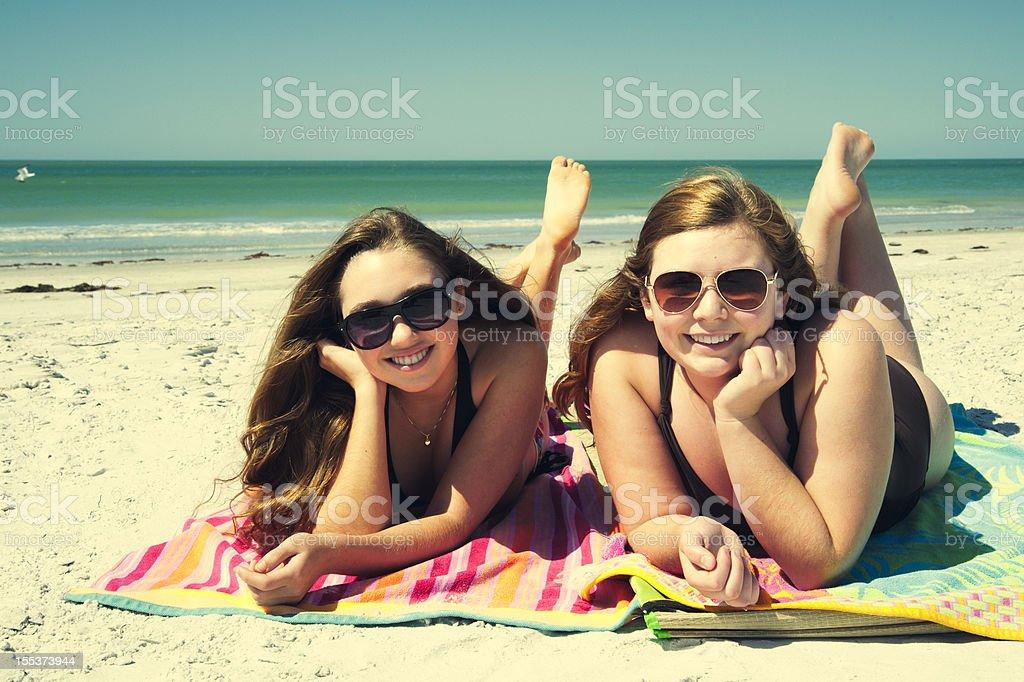 Beautiful teenagers sunbathing on the beach. royalty-free stock photo