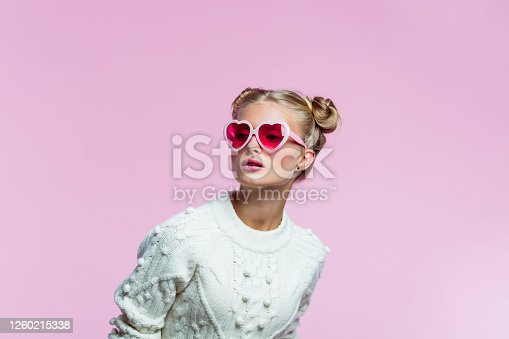 Portrait of teenager wearing white sweater and pink heart shaped sunglasses. Studio shot on pink background.