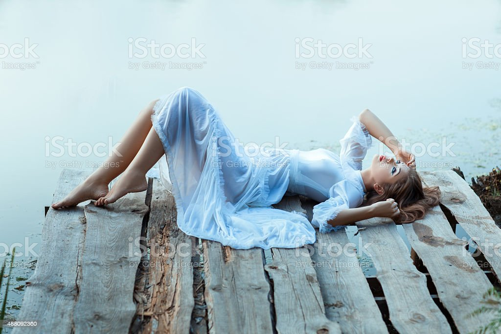 Beautiful  tender woman lying on the jetty and bored. stock photo