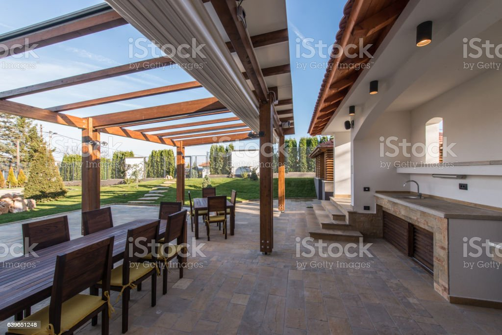 Beautiful terrace lounge with pergola and wooden table with chairs stock photo