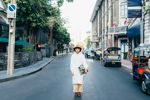 A beautiful Asian woman wearing vintage clothes standing in the street in Bangkok
