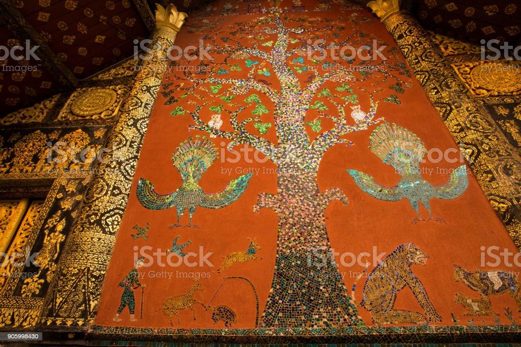 Beautiful the west facade with its painted-mosaic art tree of life  at Wat Xieng Thong temple, Luang Prabang, Laos. stock photo
