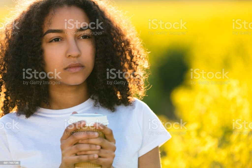 Beautiful thoughtful mixed race African American girl teenager female young woman smiling drinking takeaway coffee outside in field of yellow flowers stock photo