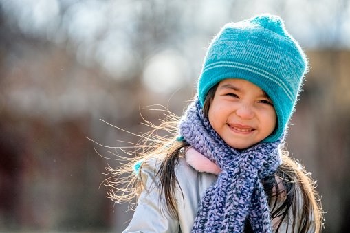 Beautiful Three-year-old Mixed Race Girl Smiling and Playing in her Backyard Dressed up Warmly for Winter Fun