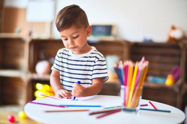 Beautiful toddler boy drawing cute draw using colored pencils at kindergarten stock photo
