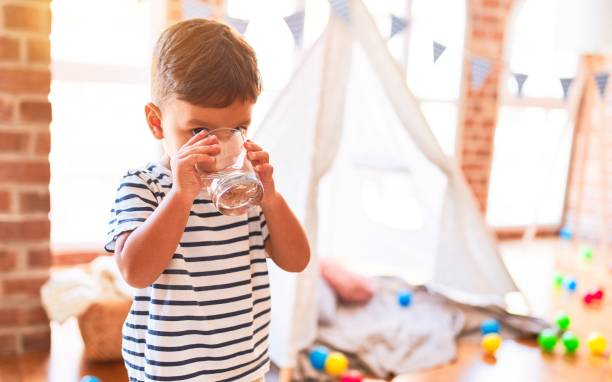Beautiful toddler boy drinking glass of water at kindergarten stock photo