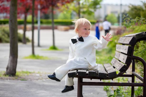 Hermoso niño pequeño en esmoquin, jugando en un parque en un día de la boda - foto de stock