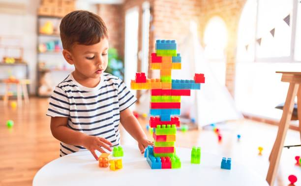 Beautiful toddler boy playing with construction blocks at kindergarten stock photo