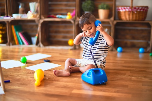 Beautiful toddler boy playing with vintage blue phone at kindergarten