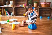 istock Beautiful toddler boy playing with vintage blue phone at kindergarten 1185932041