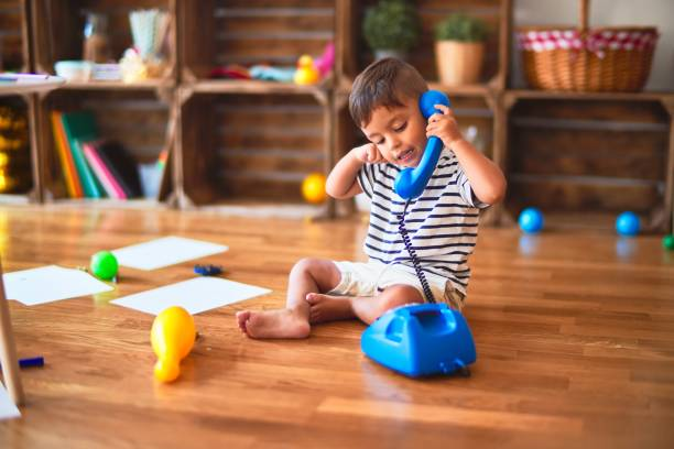 Beautiful toddler boy playing with vintage blue phone at kindergarten stock photo