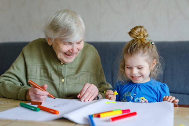Beautiful toddler girl and grand grandmother drawing together pictures with felt pens at home. Cute child and senior woman having fun together. Happy family indoors stock photo