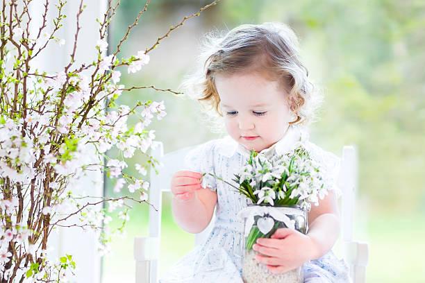 schönes mädchen holding ersten frühling blumen in transparente vase - geschenk zur taufe stock-fotos und bilder