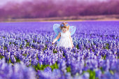 美しい幼児の女の子の妖精のコスチュームでプレーするフラワーフィールド