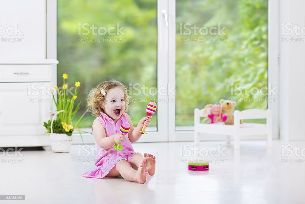 Beautiful toddler girl playing tambourine in nursery with big window stock photo