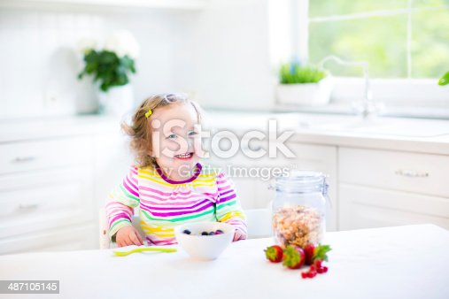 istock Beautiful toddler girl with curly hair in white sunny kitchen 487105145
