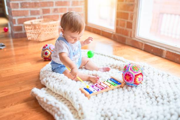 Beautiful toddler sitting on the blanket playing xylophone smiling at kindergarten stock photo