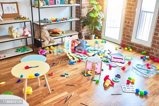 istock Beautiful toddler sitting on the floor playing with building blocks toy at kindergarten 1185943124