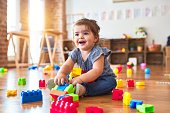 Beautiful toddler sitting on the floor playing with building blocks toys at kindergarten