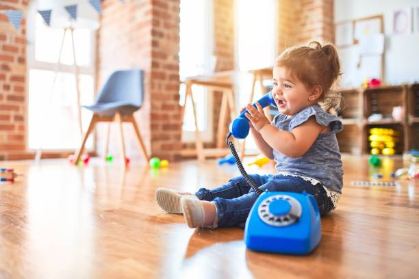 Beautiful toddler sitting on the floor playing with vintage phone at kindergarten stock photo