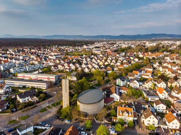 Schöne Aussicht auf eine Kirche, Schule und Häuser in einer deutschen Stadt. Orange Ziegeldächer. Berge und der blaue Himmel im Hintergrund. Die Straßen einer kleinen deutschen Stadt. – Foto