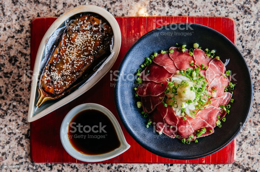 Beautiful top view of Nasu Dengaku - Beef Takaki - Japanese grilled eggplant and sliced raw beef with miso and soy sauce stock photo