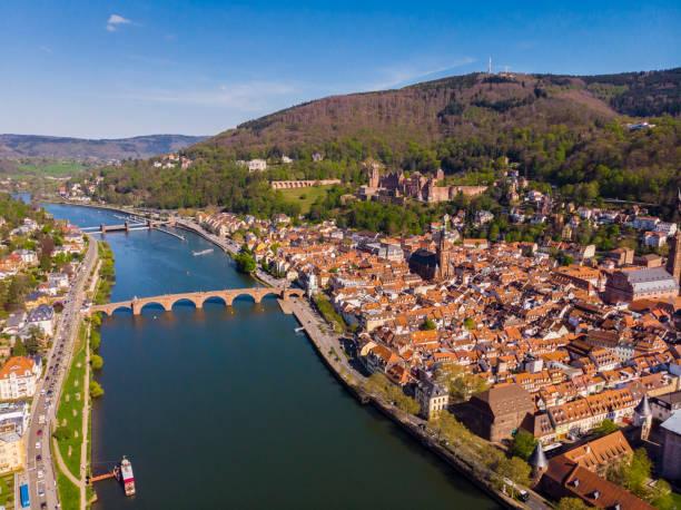 Schöne Aussicht auf das Heidelberger Schloss und die Altstadt. Frühling. Grüne Blätter auf den Bäumen. Nekka River. Fußgängerbrücke über den Fluss. Schöne Berge. – Foto
