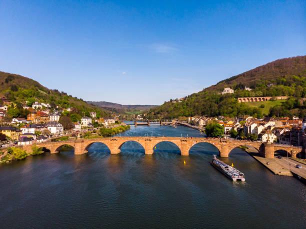 Schöne Aussicht auf die Fußgängerbrücke über den Fluss und die Altstadt. Frühling. Grüne Blätter auf den Bäumen. Nekka River. Schöne Berge. Heidelberg. Deutschland. – Foto