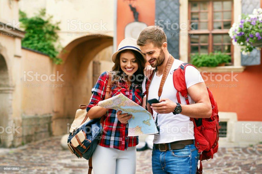 Pareja de turistas hermoso viaje teléfono y usando el mapa. - Foto de stock de Actividad de fin de semana libre de derechos