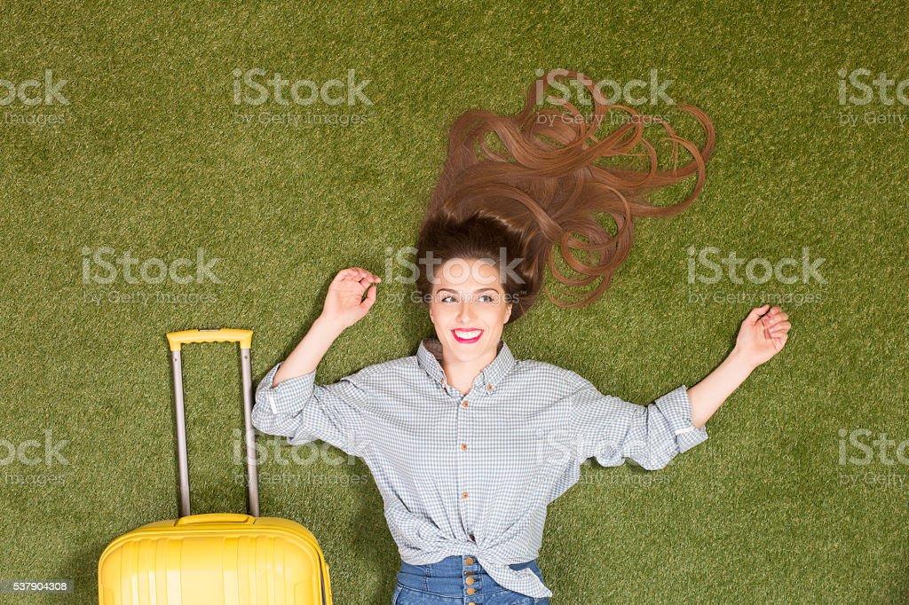 Beautiful tourist lady lying on green grass stock photo