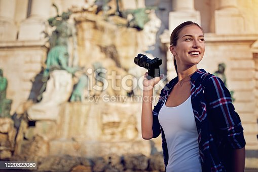 istock Beautiful tourist woman is taking pictures of famous places 1220322080