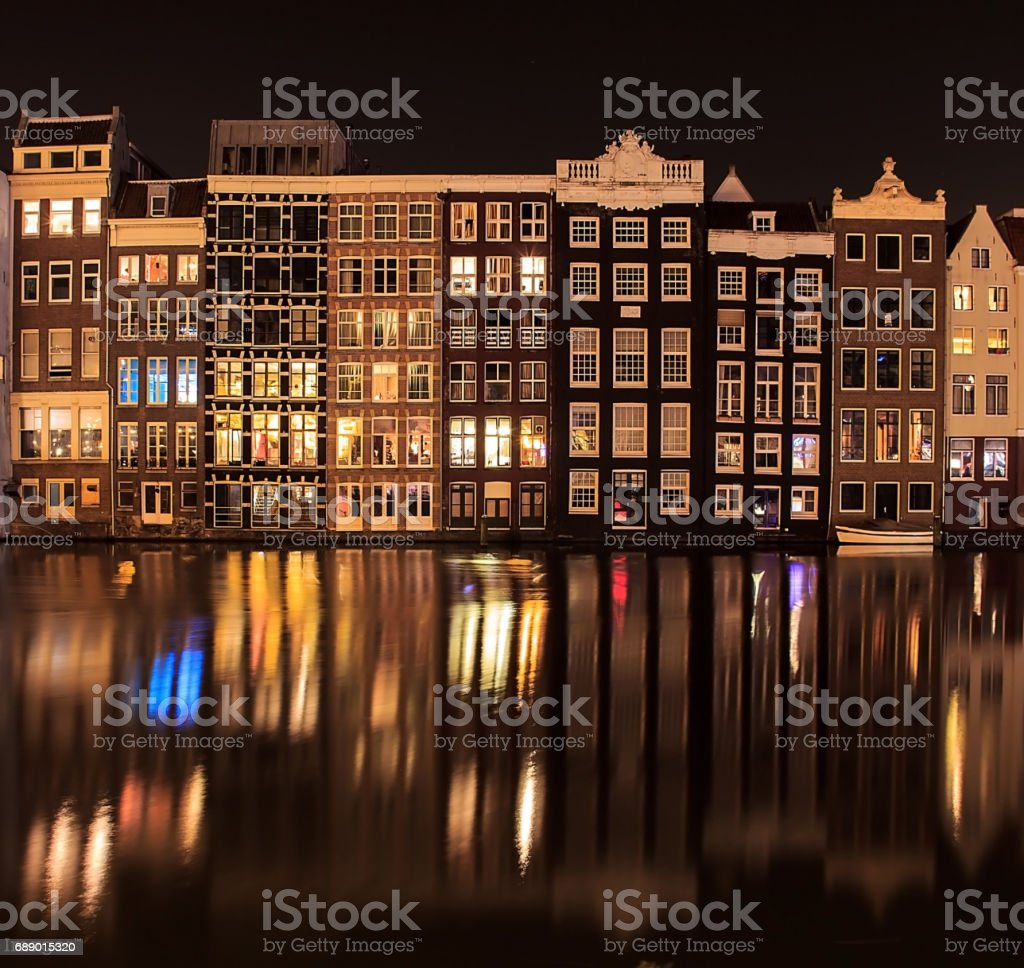 Beautiful traditional old buildings at night with reflection in Amsterdam, the Netherlands stock photo