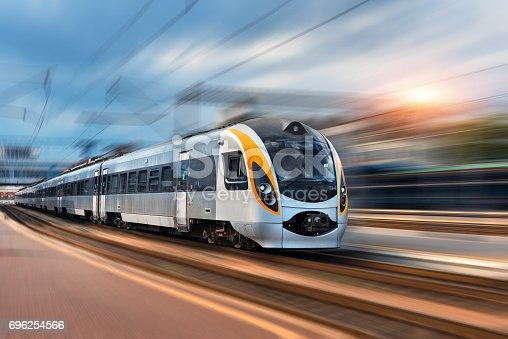istock Beautiful train in motion at the railway station at sunset in Europe. Modern intercity train on the railway platform with motion blur effect. Industrial landscape with passenger train on railroad 696254566