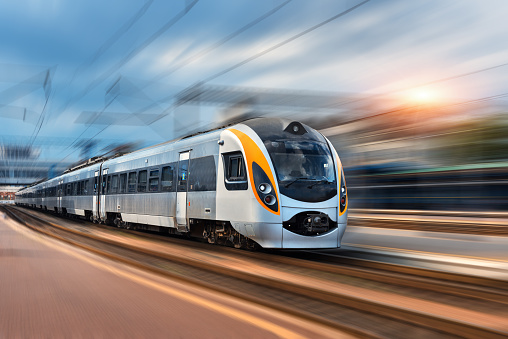 Beautiful train in motion at the railway station at sunset in Europe. Modern intercity train on the railway platform with motion blur effect. Industrial landscape with passenger train on railroad
