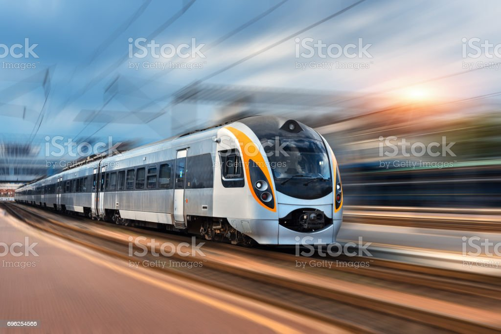 Beautiful train in motion at the railway station at sunset in Europe. Modern intercity train on the railway platform with motion blur effect. Industrial landscape with passenger train on railroad stock photo