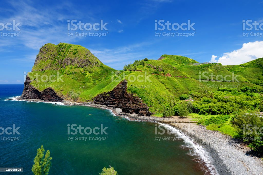 Beautiful tranquil view of Maui landscape with white clouds over green fields stock photo