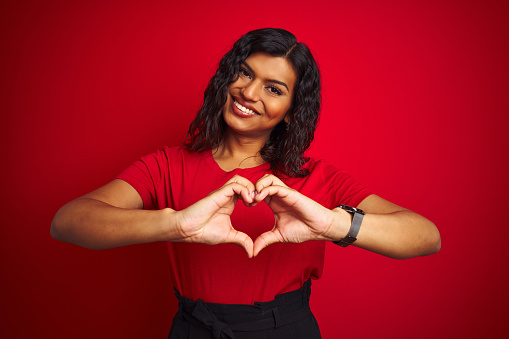 Beautiful transsexual transgender woman wearing t-shirt over isolated red background smiling in love doing heart symbol shape with hands. Romantic concept.