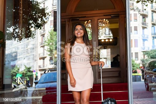 Portrait of a beautiful traveling woman exiting the hotel carrying her luggage and smiling - travel concepts