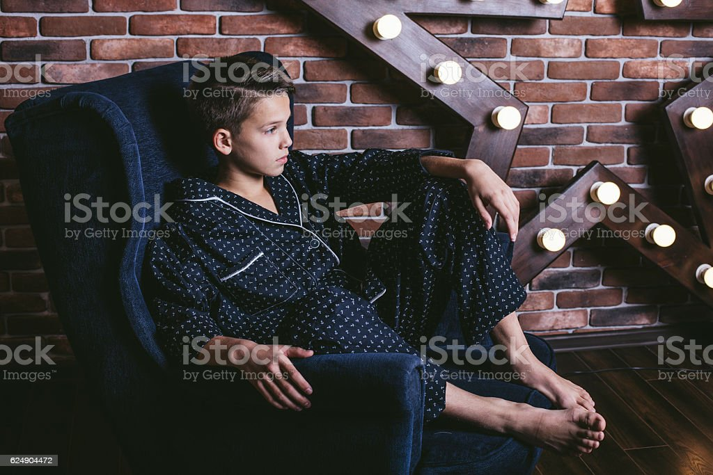 Beautiful trendy teen boy sitting on a chair at home - Photo