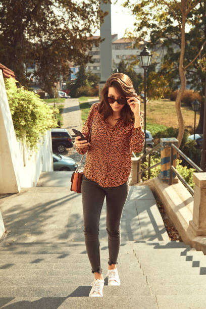 Beautiful trendy woman using cellphone on the street. stock photo