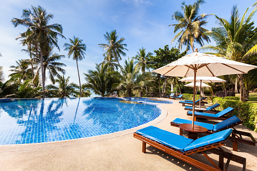 istock Beautiful tropical beach front hotel resort with swimming pool, sunshine 641448082
