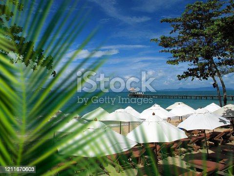 Beautiful tropical beach with beach umbrellas, wooden pier and blue sea water over blue sky in Phuket island, Thailand