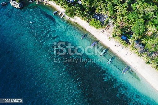 An idyllic tropical scene of sand, sun, boats, and water on the beautiful island of Guimaras, Western Visayas, Philippines.