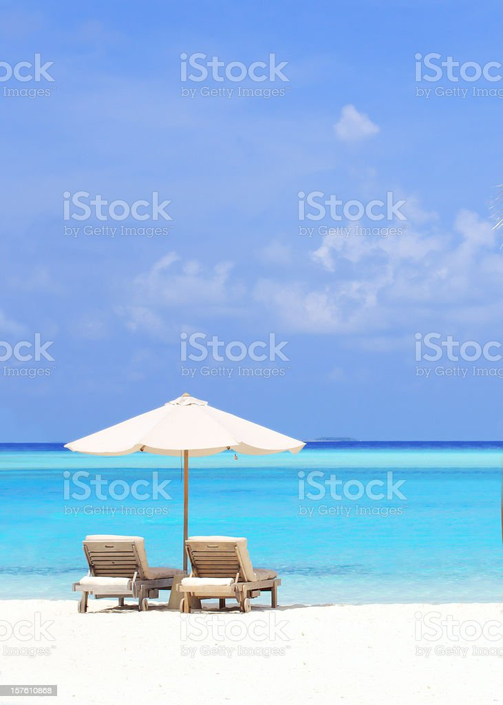Beautiful tropical beach with deck chairs and parasol. royalty-free stock photo