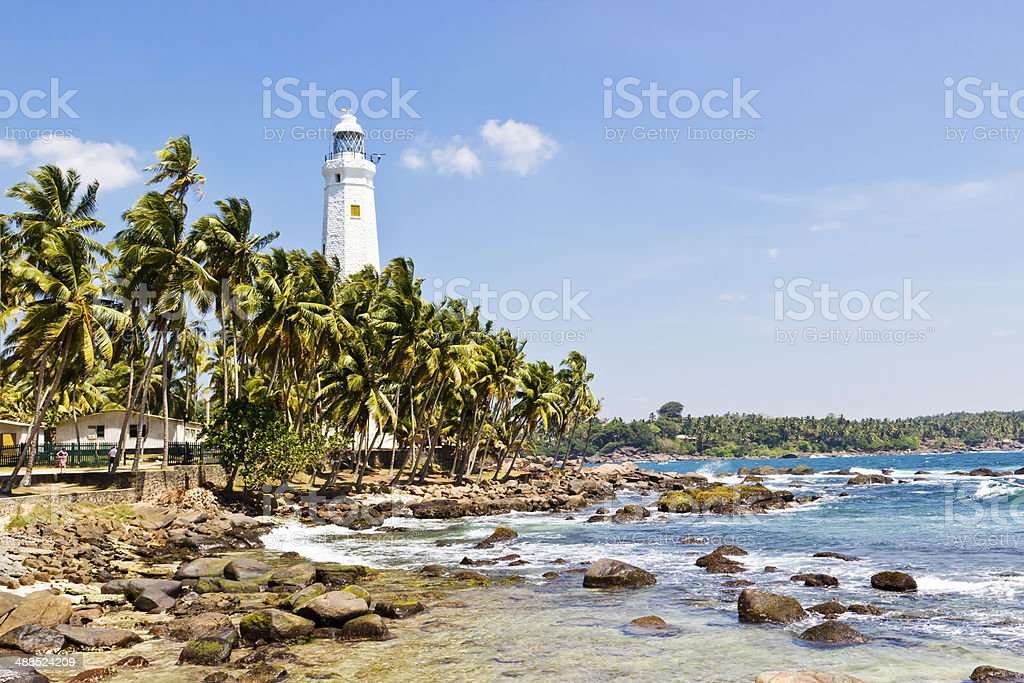 Beautiful tropical landscape with white Dondra Head Lighthouse and palms stock photo