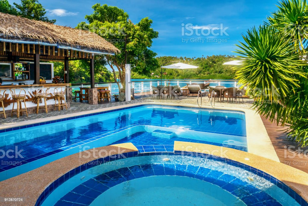 A beautiful tropical resort swimming pool with vibrant blue colors and an open-air bar with thatched roof set on the edge of a saltwater bay in the Philippines. stock photo