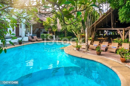 A large, bright blue swimming pool with marble stone tiles fills most of the frame, along with a tropical garden and poolside furniture, surrounded by resort buildings with thatched roofs .