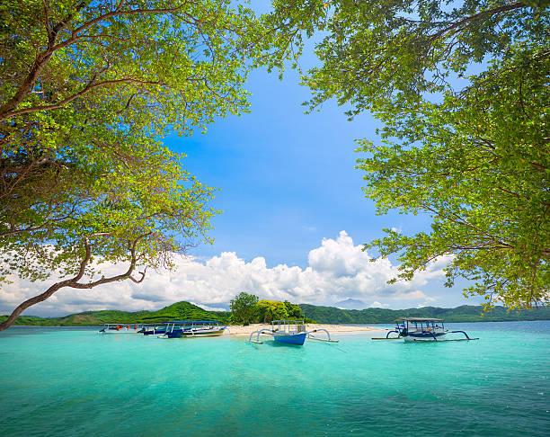 beautiful tropical uninhabited island on background of mountains. - lombok stockfoto's en -beelden